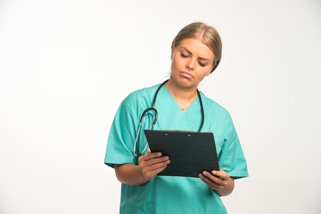 Blonde ärztin in blauer uniform hält ein quittungsbuch und prüft es sorgfältig.