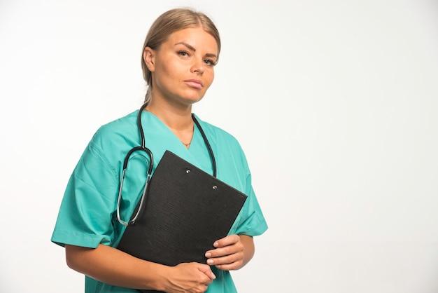 Blonde ärztin in blauer uniform hält ein quittungsbuch und sieht zuversichtlich aus.