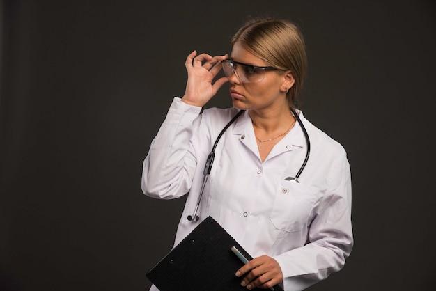 Blonde ärztin mit einem stethoskop, das brillen trägt und ein quittungsbuch hält
