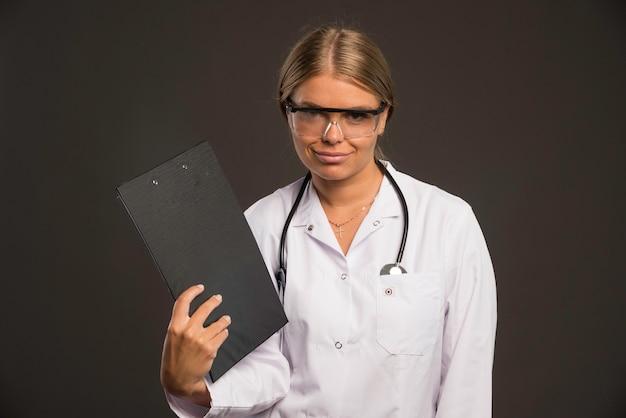 Blonde ärztin mit einem stethoskop, das eine brille trägt und sich mit dem quittungsbuch bläst.