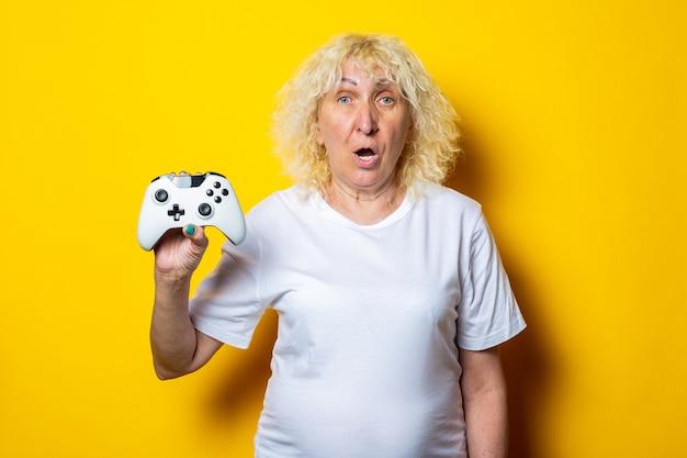 Blonde alte frau mit überraschung hält einen joystick