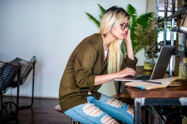 Blonde asiatische frau, die an einem laptop arbeitet