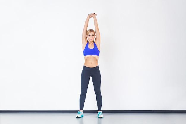Blonde athletische frau die hände hoch und macht fitnessübungen. studioaufnahme