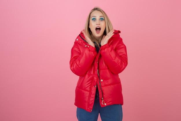Blonde attraktive aktive frau, die auf rosa wand in der bunten winter-daunenjacke der roten farbe aufwirft, spaß hat, warmen mantelmodetrend, überraschten schockierten gesichtsausdruck