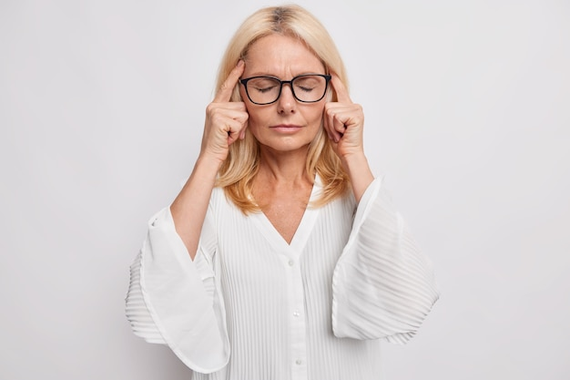 Blonde attraktive frau mittleren alters hält die finger an den schläfen leidet unter kopfschmerzen versucht sich an etwas wichtiges zu erinnern steht mit geschlossenen augen trägt eine brille weiße bluse steht vor einem schwierigen problem