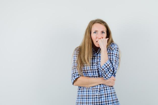 Blonde dame beißt emotional in hemd faust und sieht ängstlich aus.