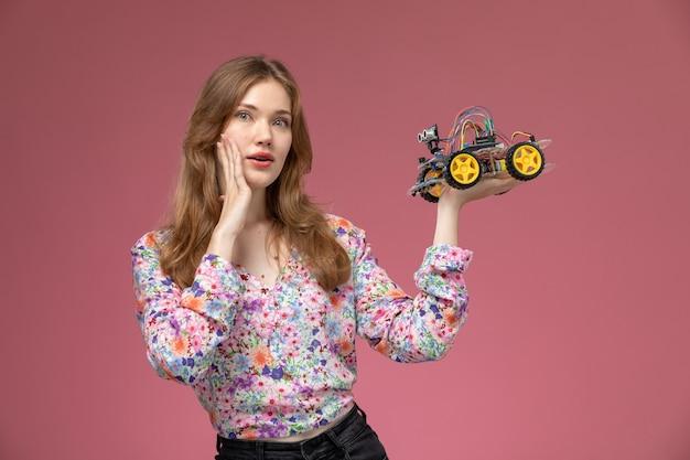 Blonde dame der vorderansicht, die durch seltsames autospielzeug überrascht wird