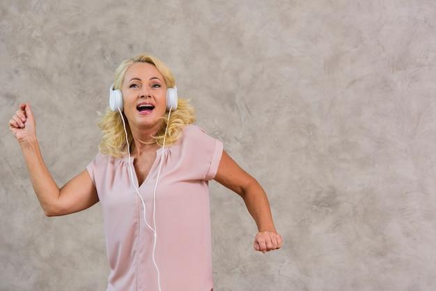 Blonde dame der vorderansicht, die musik auf kopfhörersatz hört