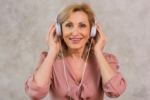 Blonde dame des smiley, die musik auf kopfhörersatz hört