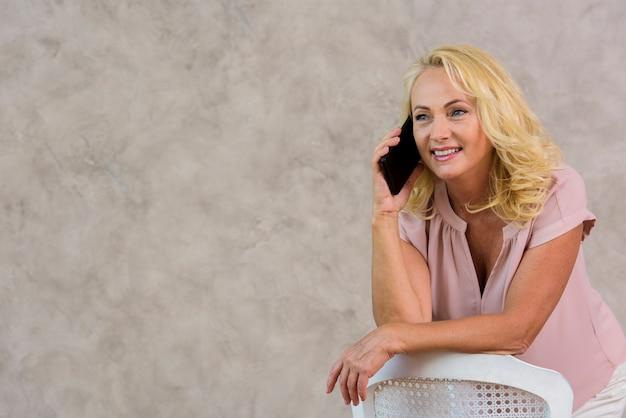 Blonde dame, die am telefon mit kopienraum spricht