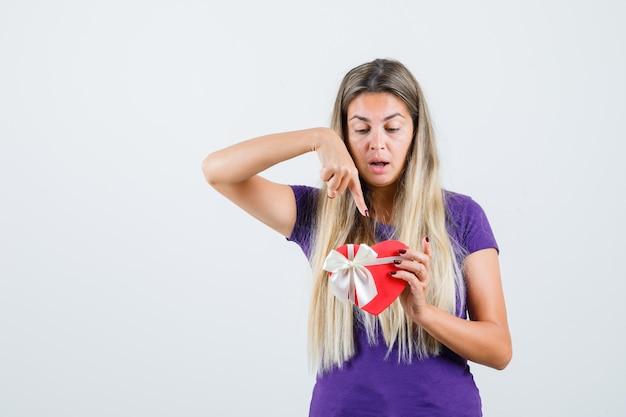 Blonde dame, die auf geschenkbox im violetten t-shirt zeigt und neugierig schaut. vorderansicht.