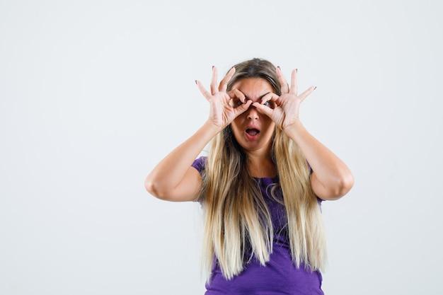 Blonde dame, die brillengeste im violetten t-shirt zeigt und erstaunt, vorderansicht schaut.