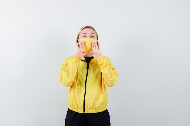 Blonde dame, die geheimnis erzählt oder etwas im trainingsanzug, in der maske ankündigt und aufgeregt schaut, vorderansicht.