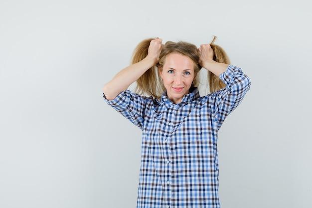Blonde dame, die haarsträhnen im hemd anordnet und niedlich aussieht.