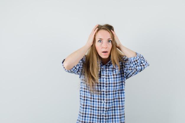 Blonde dame, die hände auf kopf im hemd hält und verwirrt schaut.