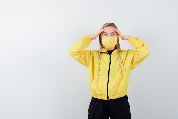 Blonde dame, die hände auf kopf im trainingsanzug, in der maske hält und nachdenklich, vorderansicht schaut.