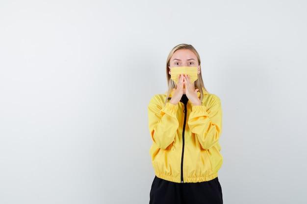 Blonde dame, die hände auf mund im trainingsanzug, in der maske hält und ängstlich, vorderansicht schaut.