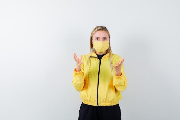 Blonde dame, die hände im trainingsanzug, in der maske hebt und verwirrt aussieht. vorderansicht.