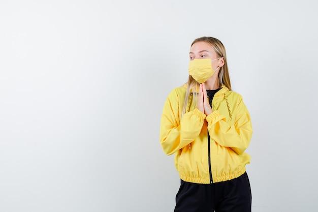 Blonde dame, die hände in der gebetsgeste im trainingsanzug, in der maske hält und nachdenklich schaut, vorderansicht.