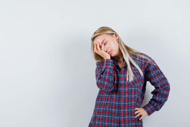 Blonde dame, die hand auf gesicht im freizeithemd hält und schläfrig, vorderansicht schaut.