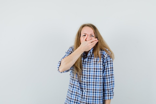 Blonde dame, die hand auf mund im hemd hält und traurig schaut.