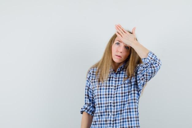 Blonde dame, die hand auf stirn im hemd hält und bedauernd schaut.