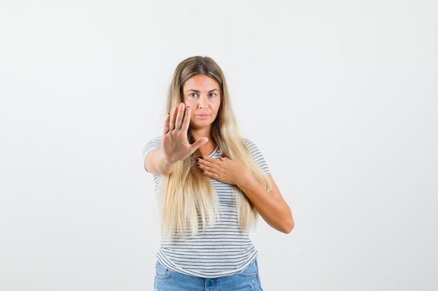 Blonde dame, die ihre hand auf ablehnende weise im t-shirt hebt und ernst aussieht. vorderansicht.