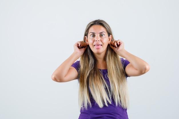 Blonde dame, die ihre ohrläppchen im violetten t-shirt herunterzieht und lustige vorderansicht sieht.