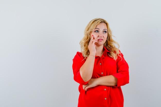 Blonde dame, die im roten hemd wegschaut und ängstlich schaut. platz für text