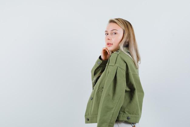 Blonde dame, die kamera in jacke, hose betrachtet und verführerisch schaut.