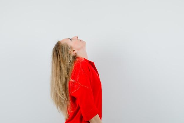 Blonde dame, die kopf in rotem hemd zurückbeugt und konzentriert schaut. .