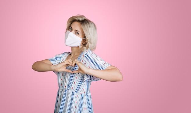 Blonde dame, die medizinische maske trägt, die das herz- und liebeszeichen in einem sommerkleid auf rosa wand gestikuliert