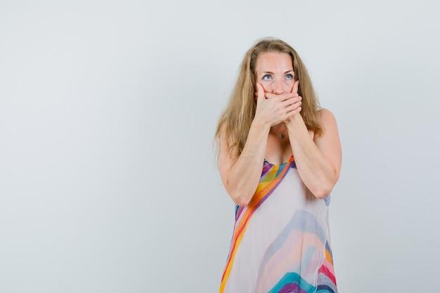 Blonde dame, die mund mit händen im sommerkleid bedeckt und schockiert schaut