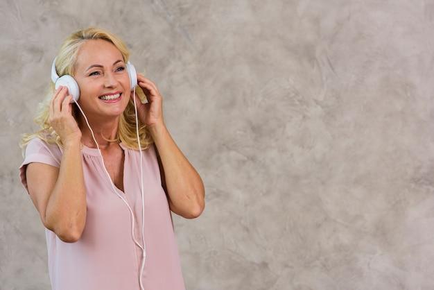 Blonde dame, die musik auf kopfhörersatz hört
