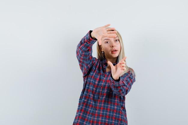 Blonde dame, die rahmengeste im freizeithemd macht und zuversichtlich schaut. vorderansicht.