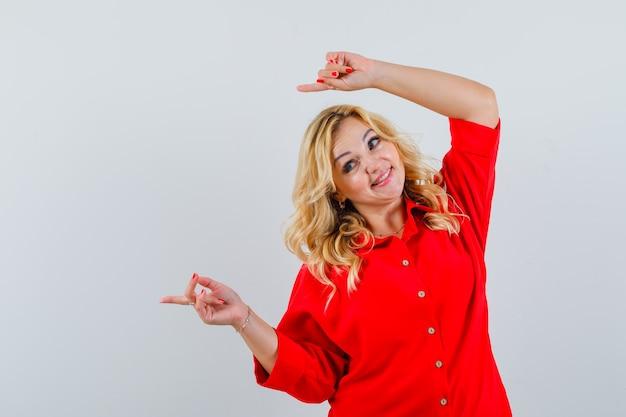 Blonde dame, die über kopf im roten hemd beiseite zeigt