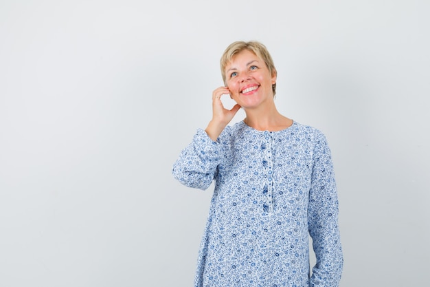 Blonde dame, die wie telefonieren in gemusterter bluse aufwirft und optimistisch, vorderansicht schaut. platz für text
