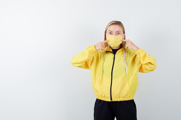 Blonde dame hält finger auf ihrer medizinischen maske im trainingsanzug und schaut vorsichtig, vorderansicht.