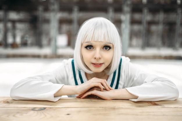 Blonde dame im anime-stil mit kaltem gesicht. cosplay mode, japanische kultur, glamourpuppe im kleid, süße frau mit make-up im fabrikladen