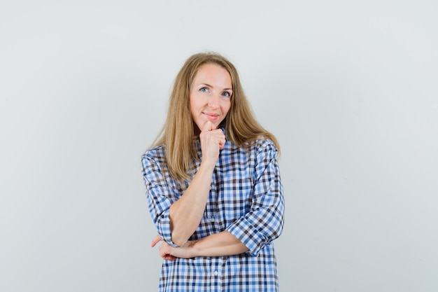 Blonde dame im hemd, das in der denkenden haltung steht und optimistisch schaut,