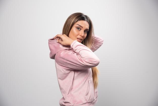 Blonde dame im rosa sweatshirt, das auf elegante und verführerische weise aufwirft.