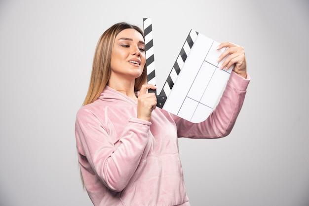 Blonde dame im rosa sweatshirt hält eine leere klappe und gibt positive und lustige posen.