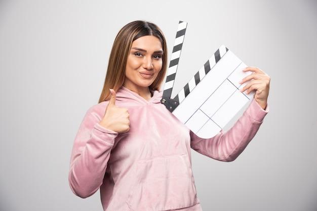 Blonde dame im rosa sweatshirt hält eine leere klappe und gibt professionelle posen.