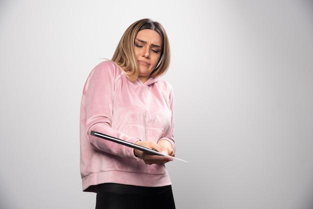 Blonde dame im rosa sweatshirt hält eine leere klappe und versucht zu verstehen, was es ist.