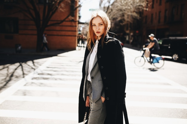 Blonde dame im schwarzen mantel steht auf der sonnigen straße irgendwo in new york city