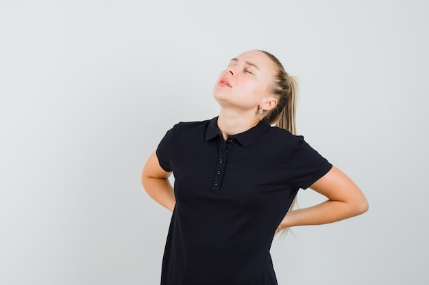 Blonde dame im schwarzen t-shirt, das unter rückenschmerzen leidet und erschöpft aussieht, vorderansicht.