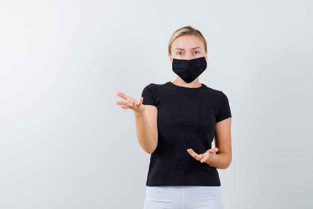 Blonde dame im schwarzen t-shirt, schwarze maske, die hände in fragender geste isoliert hält keeping