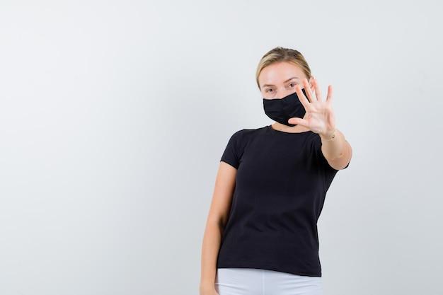 Blonde dame im schwarzen t-shirt, schwarze maske mit stopp-geste und selbstbewusstem blick