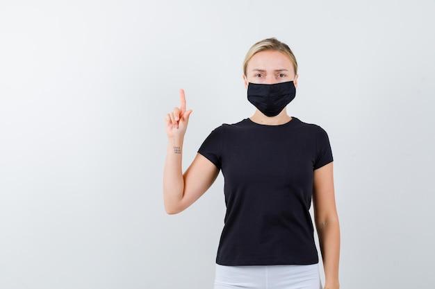 Blonde dame im schwarzen t-shirt, schwarze maske zeigt nach oben und sieht isoliert selbstbewusst aus