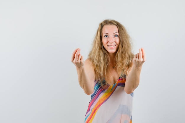 Blonde dame im sommerkleid gestikuliert mit den fingern und sieht fröhlich aus